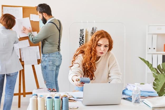 Vista frontal da estilista trabalhando no ateliê com colegas e laptop