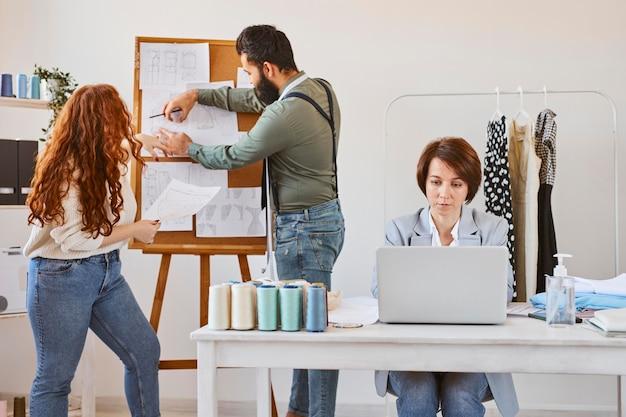 Vista frontal da estilista trabalhando no ateliê com laptop e colegas