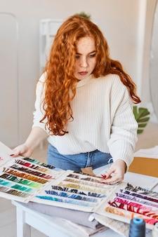 Vista frontal da estilista trabalhando no ateliê com paleta de cores