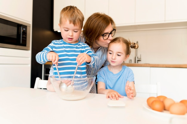 Vista frontal da família cozinhando em casa