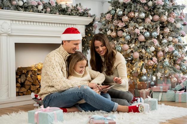 Vista frontal da família e da árvore de natal