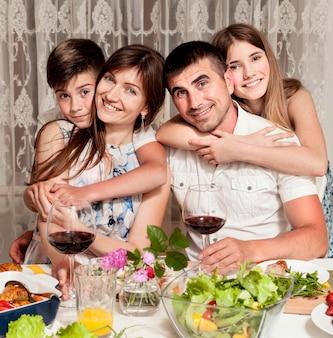 Vista frontal da família feliz na mesa de jantar com vinho