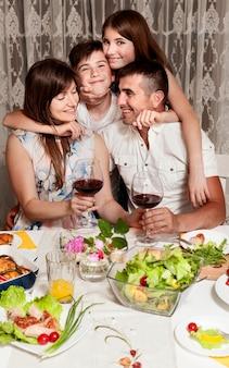Vista frontal da família feliz na mesa de jantar