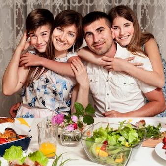 Vista frontal da família feliz posando na mesa de jantar