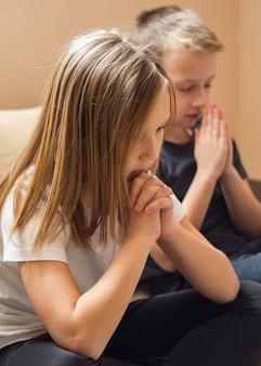 Vista frontal da família rezando