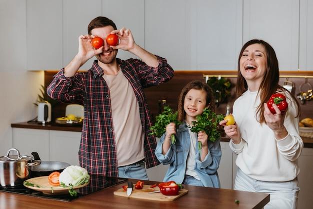 Vista frontal da família se divertindo enquanto prepara a comida na cozinha