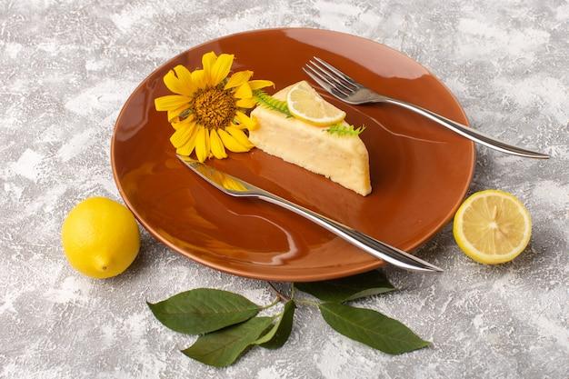Vista frontal da fatia de bolo delicioso com limão dentro da placa marrom com garfos na superfície clara