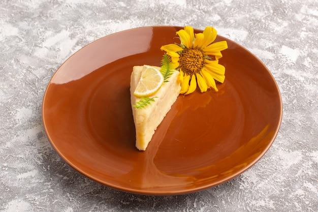 Vista frontal da fatia de bolo delicioso com limão dentro da placa marrom na mesa de luz