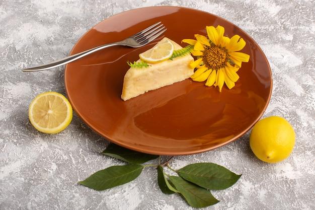 Vista frontal da fatia de bolo delicioso com limão dentro da placa marrom na superfície da luz