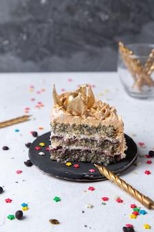 Vista frontal da fatia de bolo delicioso dentro da placa escura com velas e estrelinhas na mesa de luz
