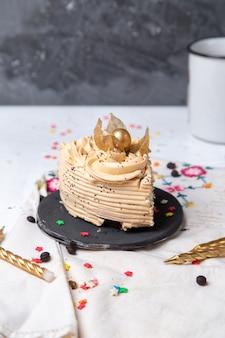 Vista frontal da fatia de bolo delicioso dentro do prato escuro com velas e estrelinhas na mesa de luz