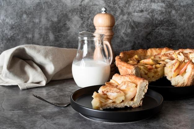 Vista frontal da fatia de torta de maçã no prato com leite