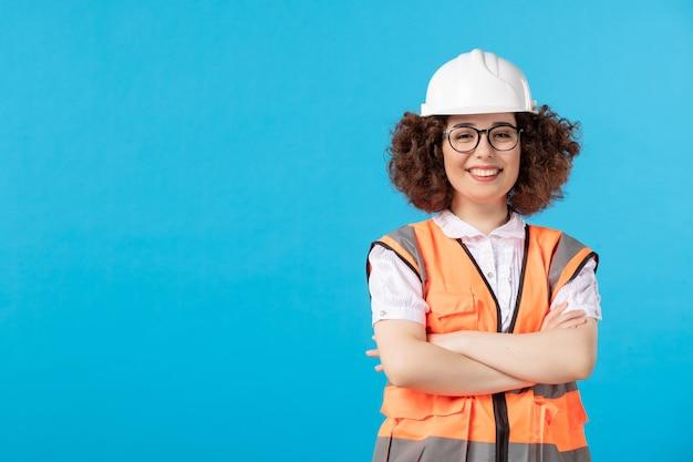 Vista frontal da feliz construtora de uniforme na parede azul
