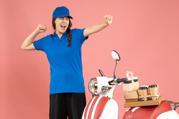 Vista frontal da feliz mensageira ao lado de uma motocicleta com café e pequenos bolos em um fundo de cor pêssego pastel