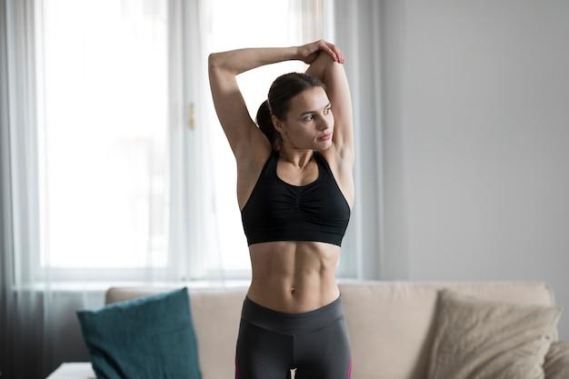 Vista frontal da fêmea alongamento em trajes esportivos