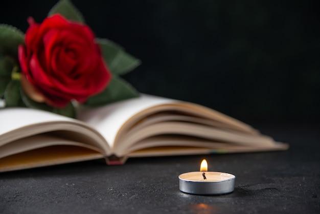 Vista frontal da flor vermelha com livro aberto no escuro