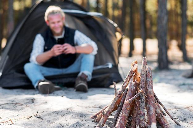 Vista frontal da fogueira de madeira e homem desfocado
