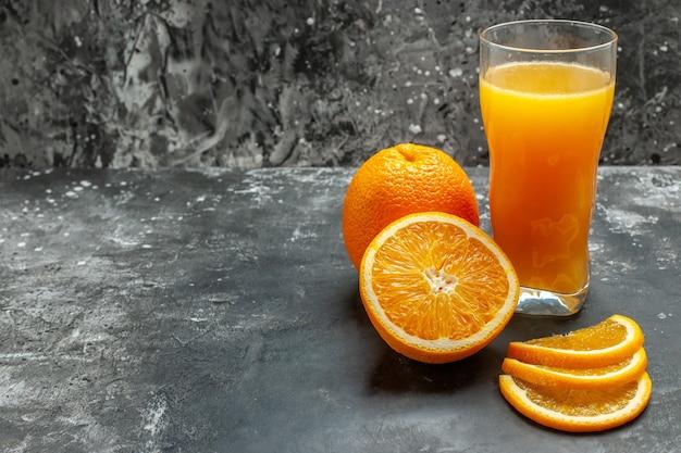 Vista frontal da fonte de vitamina cortada, laranjas frescas inteiras e inteiras e suco em fundo cinza