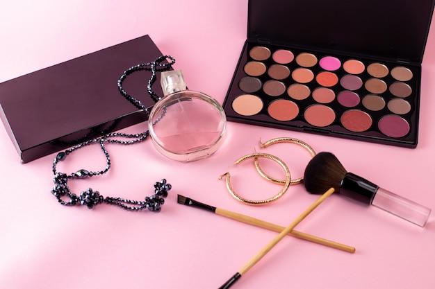 Vista frontal da fragrância elegante com colar e caixa de cosméticos preto na mesa-de-rosa