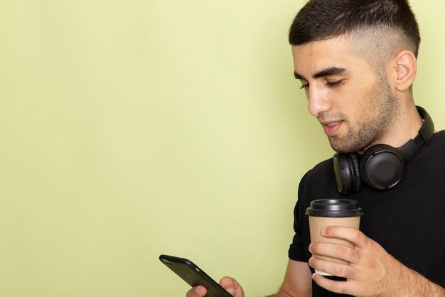 Vista frontal da frente jovem atraente masculino em camiseta preta, segurando o telefone e ouvir música, segurando a xícara de café