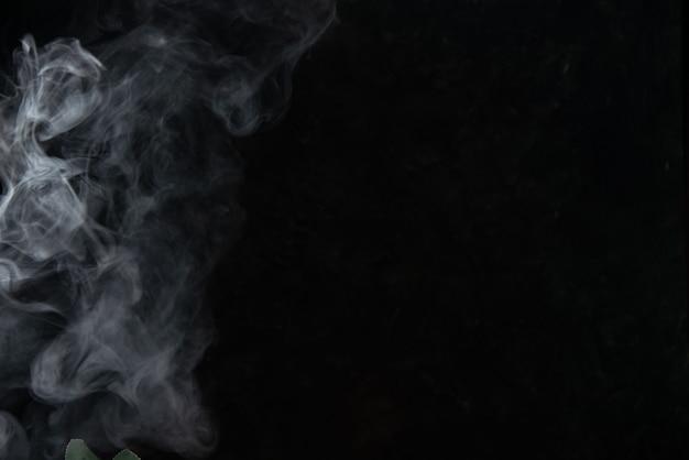 Vista frontal da fumaça leve deixada pela vela no preto