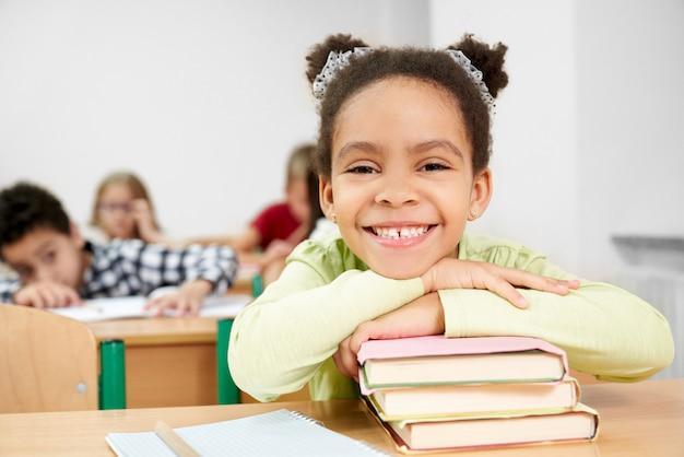 Vista frontal da garota africana feliz, deitado sobre livros e rindo