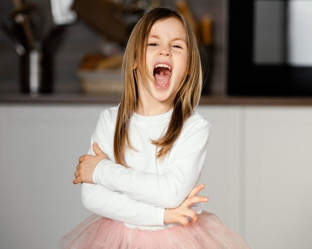 Vista frontal da garota com saia tutu e boca bem aberta