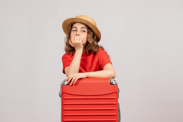 Vista frontal da garota de férias com sua mala pensando