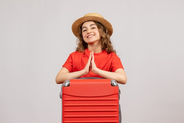 Vista frontal da garota de férias com sua valise dando as mãos