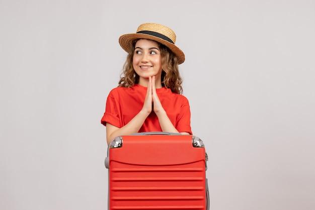 Vista frontal da garota de férias com sua valise, juntando as mãos em pé na parede branca