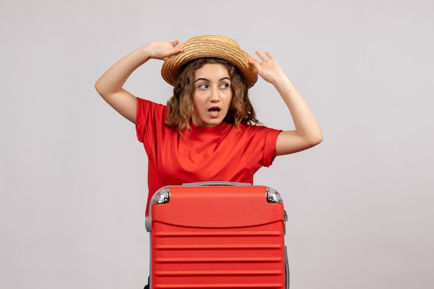 Vista frontal da garota de férias com sua valise segurando o panamá em pé na parede branca