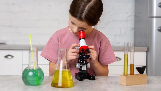 Vista frontal da garota fazendo experimentos com microscópio e tubos de ensaio