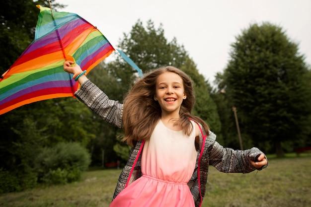 Vista frontal da garota feliz se divertindo com uma pipa