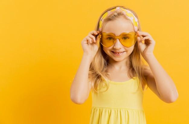 Vista frontal da garota posando com óculos de sol