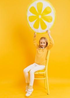 Vista frontal da garota posando enquanto segura a decoração de fatia de limão
