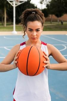 Vista frontal da garota segurando uma bola de basquete
