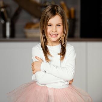 Vista frontal da garota sorridente posando com uma saia tutu