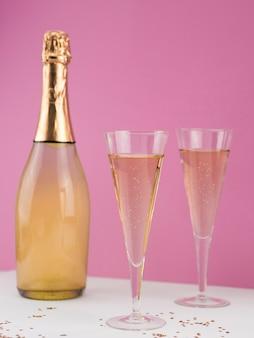 Vista frontal da garrafa de champanhe com copos cheios