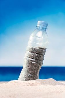 Vista frontal da garrafa de plástico cheia de areia na praia