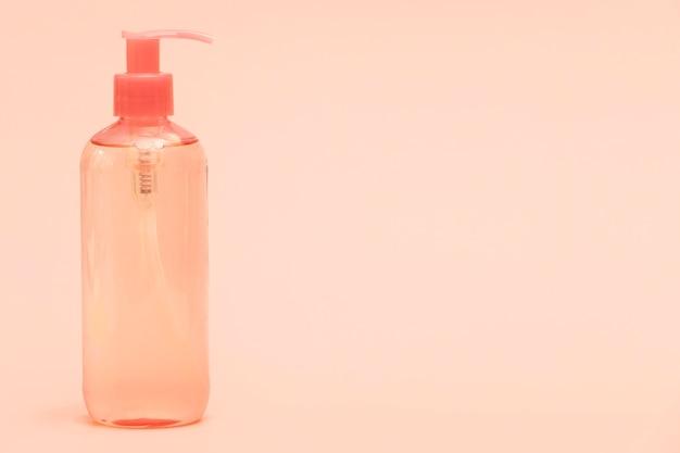 Vista frontal da garrafa de plástico com desinfetante para as mãos e cópia espaço