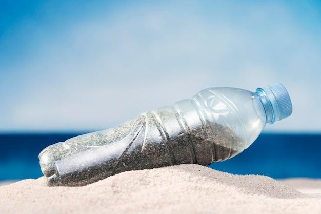 Vista frontal da garrafa de plástico na praia com areia
