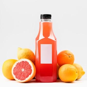 Vista frontal da garrafa de suco de toranja com tampa e frutas