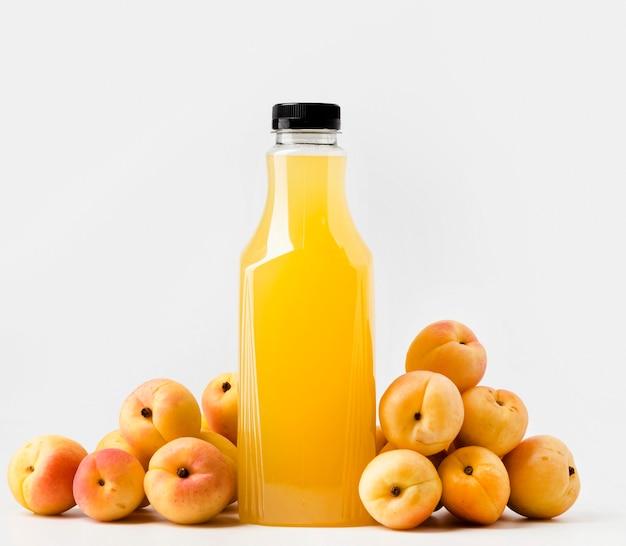 Vista frontal da garrafa de suco de vidro com pêssegos