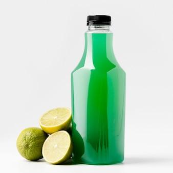 Vista frontal da garrafa de suco verde com frutas de limão