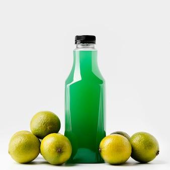 Vista frontal da garrafa de suco verde com lata e limão