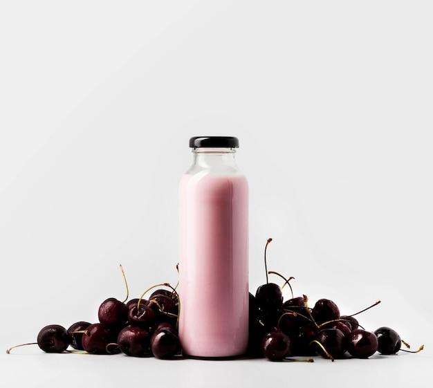 Vista frontal da garrafa de vidro com suco e cerejas