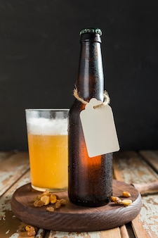 Vista frontal da garrafa de vidro de cerveja com etiqueta e nozes