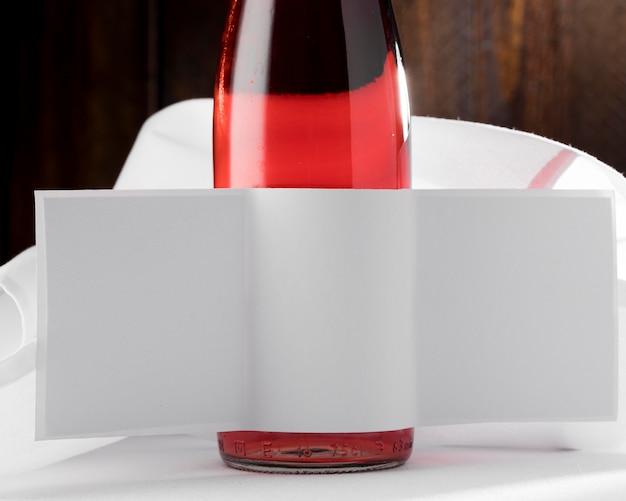 Vista frontal da garrafa de vidro de vinho com rótulo em branco