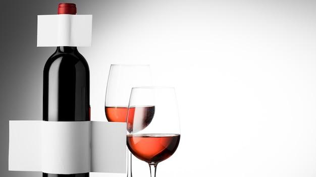 Vista frontal da garrafa de vinho com copos e rótulos em branco