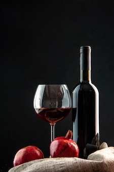 Vista frontal da garrafa de vinho com uma taça de vinho no fundo preto